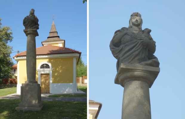 Před kaplí, na hraně travnatého svahu, stojí pískovcový sloup z 1. poloviny 19. století se sochou sv. Anežky s beránkem v náručí.