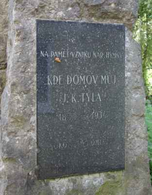 """Necelé 2 m vysoká kamenná mohyla má na čelní straně zasazenou desku s textem: """"Na paměť vzniku nár. hymny Kde domov můj a J.K. Tyla, 1834 - 1934, Sokol Tuchoměřice""""."""