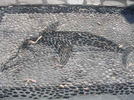 Delfín z oblázků na chodníku.
