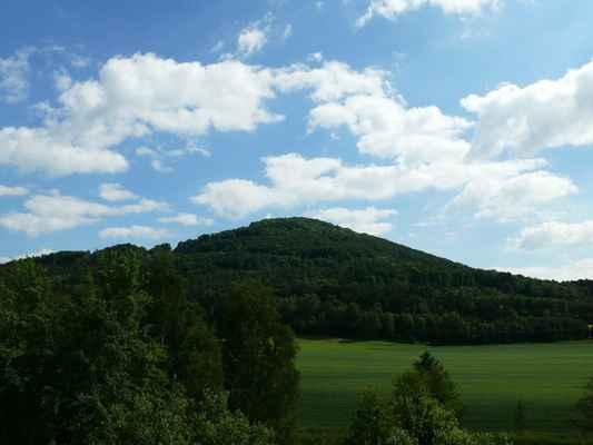 """tlustec svou výškou převyšuje okolní kopce asi o 100 m. počátkem 80. let se začal místní čedič lámat ve velkém a bylo rozhodnuto, že se celý kopec """" sníží """" o 171 m..."""